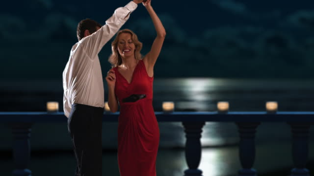 slow motion of a couple dancing on a balcony at night/marbella region, spain - slow dancing stock videos and b-roll footage