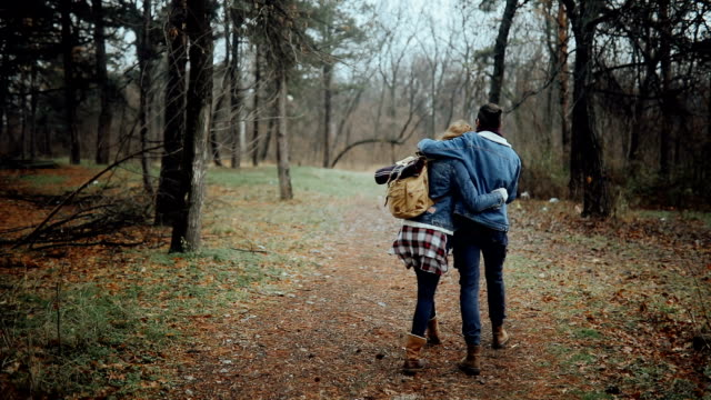 Slow motion of a couple hugging and walking on footpath in a foggy forest