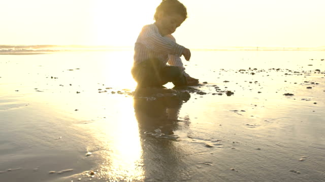 slow motion of a cute child enjoying in the beach with the sun behind him - only boys stock videos and b-roll footage