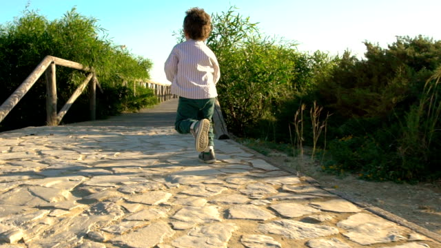 vídeos y material grabado en eventos de stock de slow motion of a cute child running and enjoying in a footpath - calzado