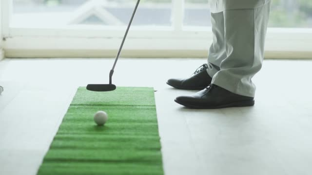 slow motion of a golf ball rolling into the hole - accuracy stock videos & royalty-free footage
