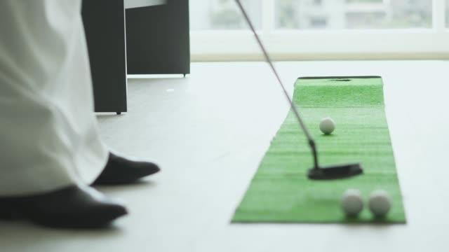 langsame bewegung eines golfballs, der ins loch rollt - minigolf stock-videos und b-roll-filmmaterial