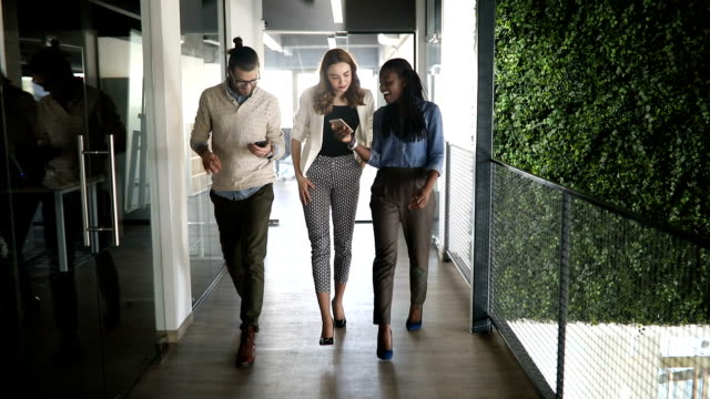 slow motion of a group of people walking in office - generazione y video stock e b–roll