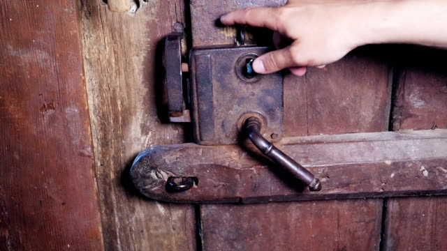 slow motion of a hand opening an ancient wooden door - legno video stock e b–roll