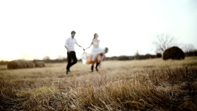 stockvideo's en b-roll-footage met slow motion van een echtpaar loopt in de wei - bruidegom