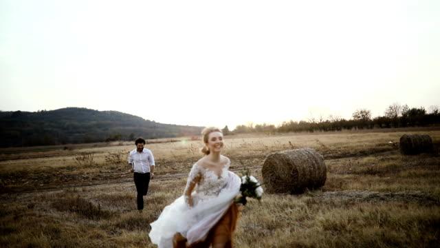 vídeos de stock e filmes b-roll de slow motion of a married couple runs in the meadow - romance