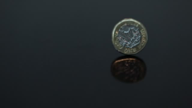 slow motion of a one pound sterling coin spinning on a table in london uk on tuesday sept 19 photographer simon dawson bloomberg - spinning stock videos & royalty-free footage