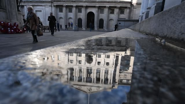 Slow motion of a pedestrians walking past a puddle reflecting the Bank of England in the City of London UK on Friday Dec 15 Photographer Chris J...