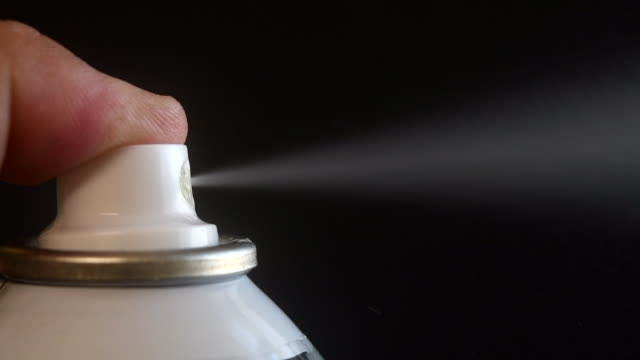 slow motion of a spray being actioned against a black background - aerosol spray stock videos & royalty-free footage