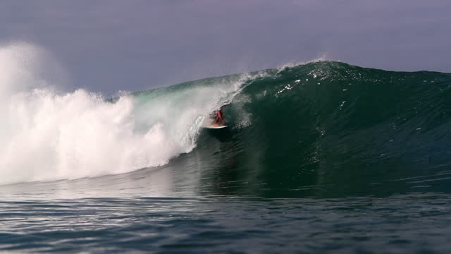 slow motion of a surfer riding in the pipeline of a breaking barrel wave as he touches the side of the wave and raises his arms at the end - oahu, hawaii - competizione video stock e b–roll