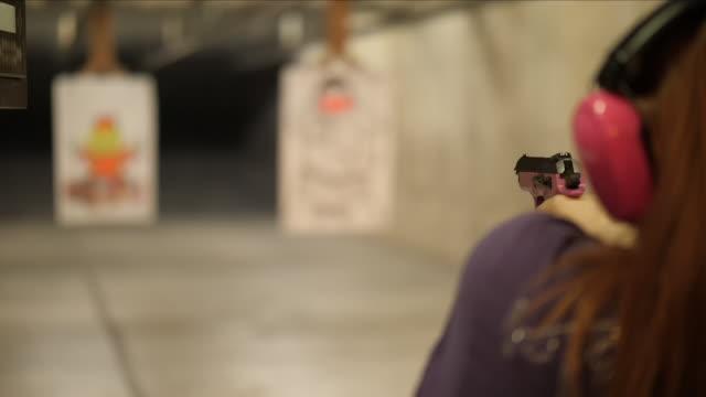 slow motion of a woman firing a gun at a shooting range - sportskytte bildbanksvideor och videomaterial från bakom kulisserna