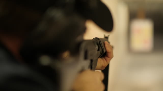 slow motion of a woman firing a gun at a shooting range - gewehr stock-videos und b-roll-filmmaterial