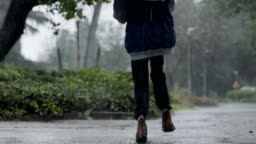 Slow motion of a young boy jumping in the pouring rain holding an umbrella