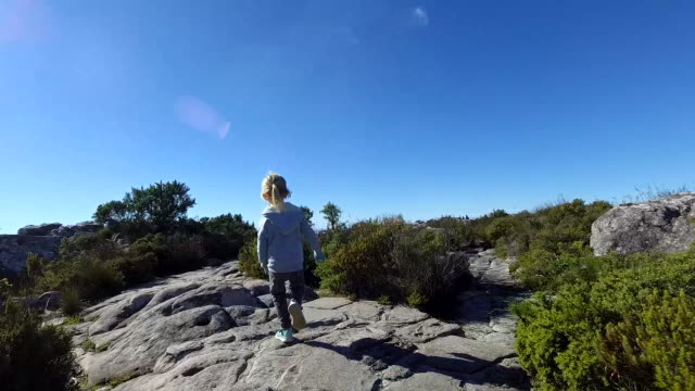 Slow motion of a young boy running along a path