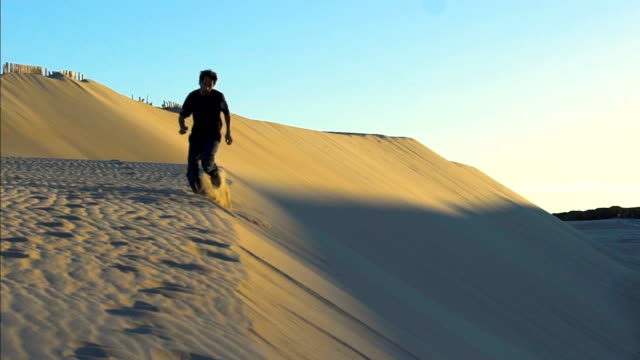 slow motion of a young man running and jumping in a dune sand - one mid adult man only stock videos & royalty-free footage