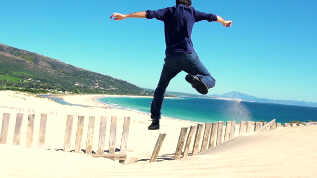 vídeos de stock e filmes b-roll de slow motion of a young man running and jumping in a dune sand - casual clothing