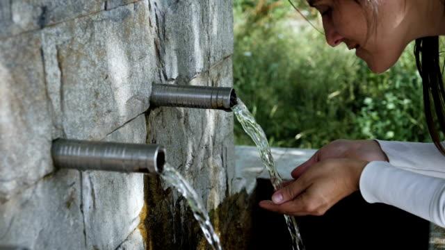 vidéos et rushes de mouvement lent d'une jeune femme appréciant l'eau pur de la montagne d'une fontaine naturelle - jet d'eau