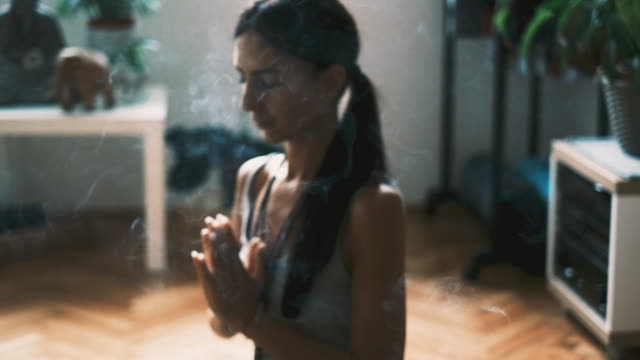 Slow motion of a young woman meditating and relaxing with incense sticks at home
