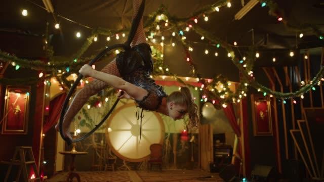 Slow motion of aerialist performing on hanging hoop in nightclub / Provo, Utah, United States