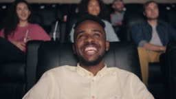 Slow motion of African American man enjoying film in cinema laughing smiling