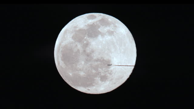 slow motion of airplane flying in front of the full moon - supermoon stock videos & royalty-free footage