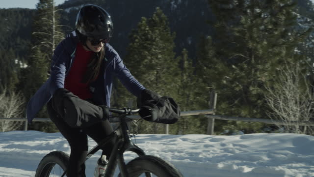 slow motion of approaching girl riding fat bike in snow / tibble fork, utah, united states - three quarter length stock videos & royalty-free footage