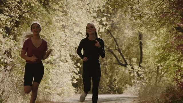 slow motion of approaching girls running on park path in autumn / american fork canyon, utah, united states - american fork canyon stock videos & royalty-free footage