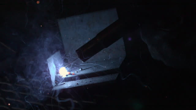 Slow motion of arc welder up close.