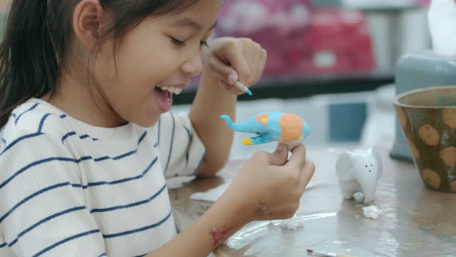 slow motion of asian child girl is painting oil color on small ceramic elephant with fun. kids arts and crafts creative activity class in school. - craft stock videos & royalty-free footage