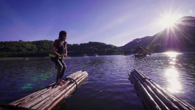 湖、旅行休暇と家族概念竹のいかだから飛び込むアジア少女のスローモーション - 桟橋点の映像素材/bロール