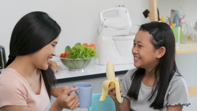 vídeos y material grabado en eventos de stock de lento movimiento de madre asiática hablando y comiendo café y plátano con hija en la cocina en casa - potasio