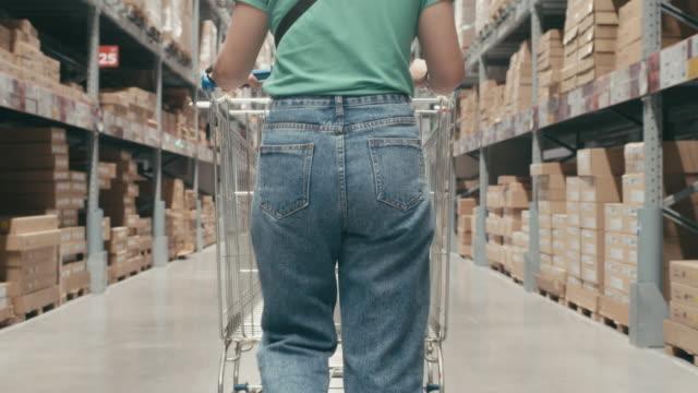 vídeos y material grabado en eventos de stock de lento movimiento de la mujer asiática comprando en el almacén moderno, la cámara se mueve de abajo a arriba - jib shot