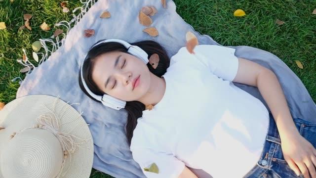 vidéos et rushes de mouvement lent de la femme asiatique dormant en écoutant la musique par des écouteurs, la fille d'asie faisant la sieste et se trouvant sur le sol de stationnement tout en portant des écouteurs en été, la technologie moderne et le concept de mode de - faire un somme
