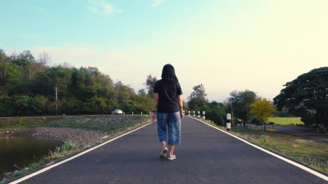 stockvideo's en b-roll-footage met slow motion van aziatische vrouw lopen op weg op de dam in ochtend met ontspannen emotie - menselijke rug
