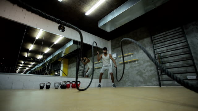 Slow motion of athletic black man doing battle ropes exercise in a gym.