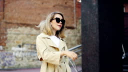 Slow motion of attractive girl listening to music through earphones using smartphone and dancing walking in the street and enjoying walk in modern city.