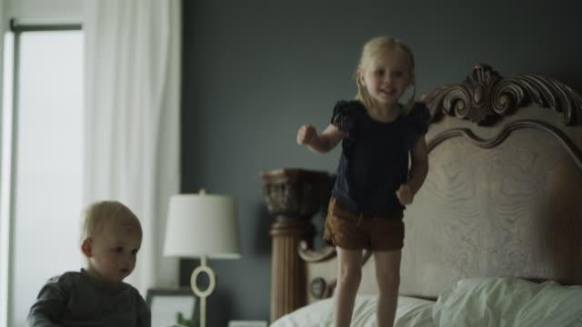 slow motion of baby boy watching sister jumping on bed / cedar hills, utah, united states - ヘッドボード点の映像素材/bロール