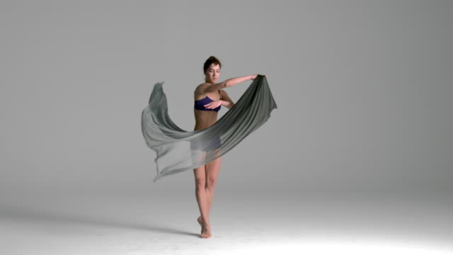 slow motion of ballerina dancing with silk fabric
