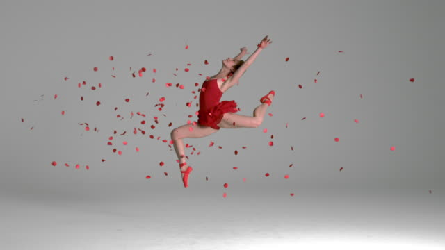 slow motion of ballerina jumping through red flowers petals - dance studio video stock e b–roll