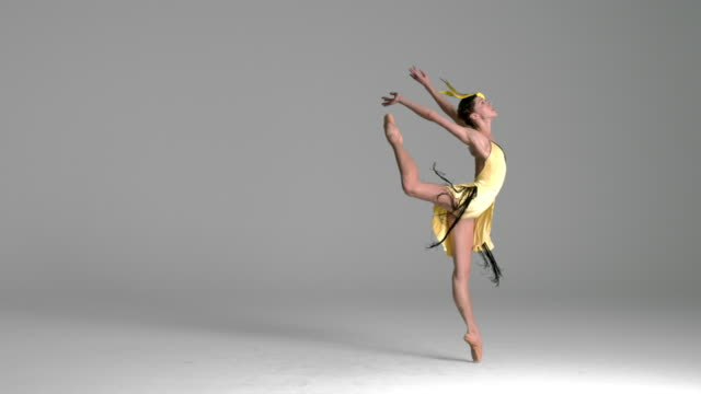 slow motion of ballerina performing, dancing in yellow bird costume