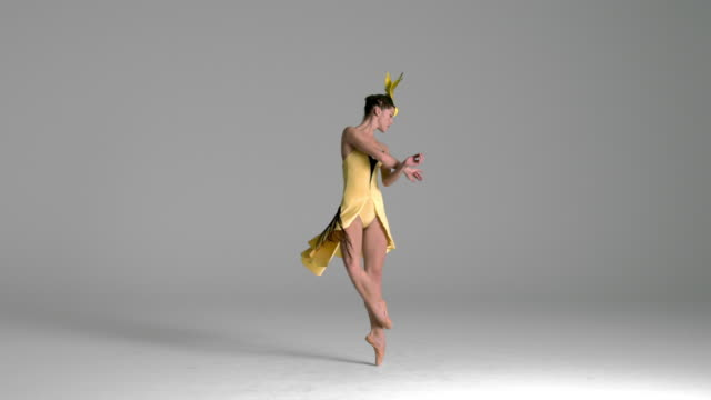vídeos de stock, filmes e b-roll de slow motion of ballerina performing, dancing in yellow bird costume - pirouette