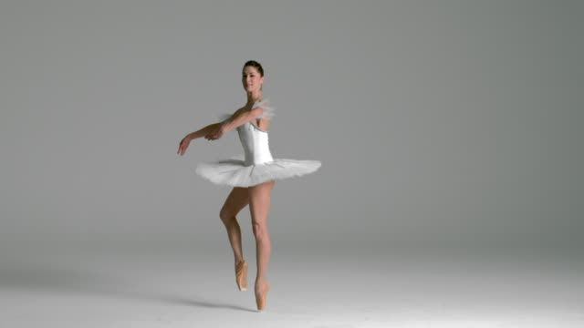 slow motion of ballerina performing pirouette in studio - balletttänzer stock-videos und b-roll-filmmaterial