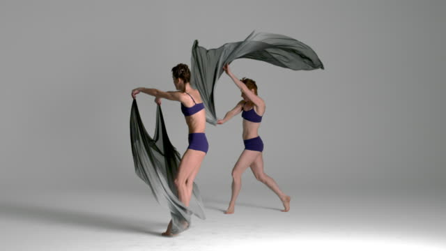 slow motion of ballerinas dancing with silk fabric