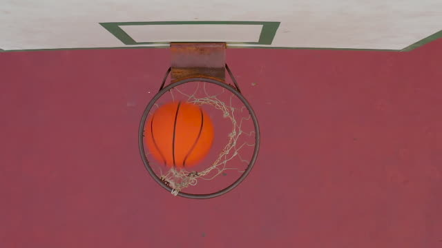 slow motion of basketball passing through a hoop on an outdoor court - basketball hoop stock videos & royalty-free footage