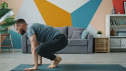 Slow motion of bearded man doing balancing yoga exercises working out in house