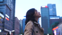 Slow Motion Of Beautiful Chinese Woman Looking Up to The Cityscape In The City