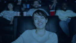 Slow motion of beautiful lady laughing watching funny film in dark cinema