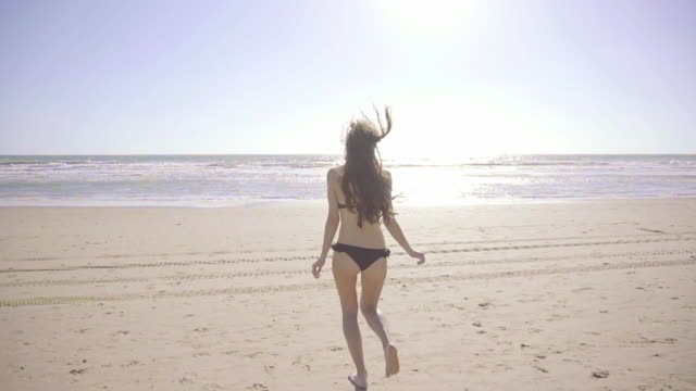 Slow motion of Beautiful woman on beach in a sunny day