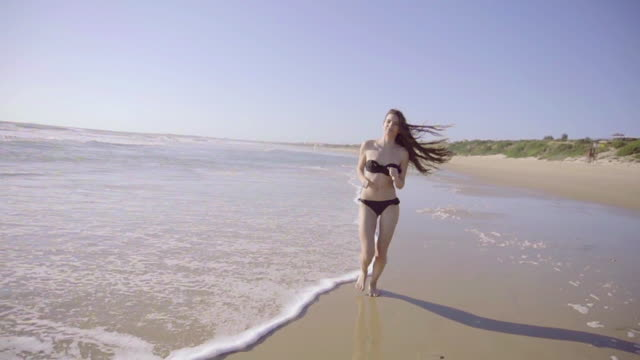 Slow motion of Beautiful woman running on beach in a sunny day