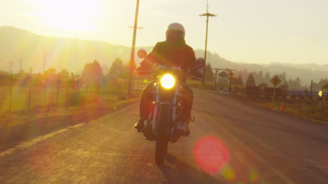 Slow motion of biker riding motorcycle on road against sky during sunset